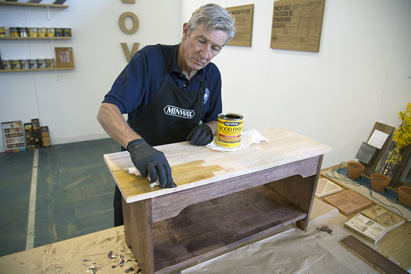 Bruce Johnson staining the top of the bench