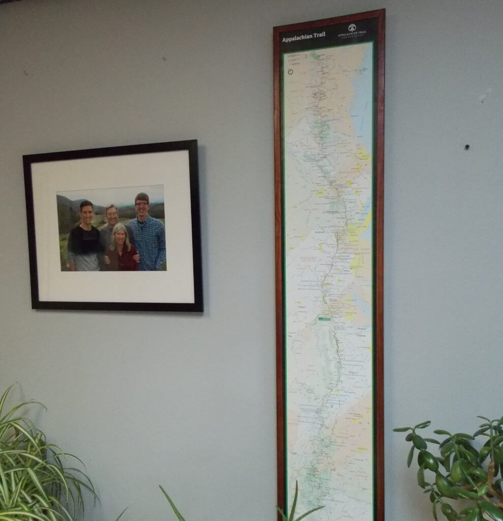 Hanging finished wood map frame on wall